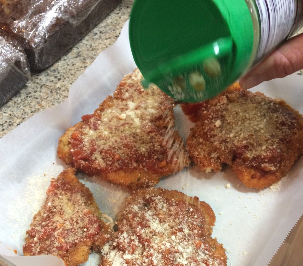 Chicken Parmesan - Sprinkling parmesan cheese over the chicken