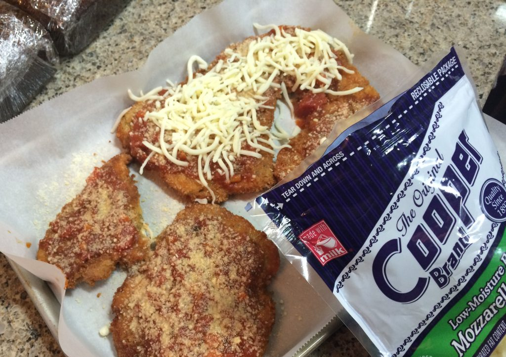 Chicken Parmesan - Sprinkling mozzarella cheese over the chicken